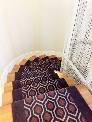 tapis violet géométrique dans un escalier en bois