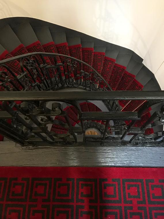 tapis rouge et noir graphique dans un escalier tournant noir