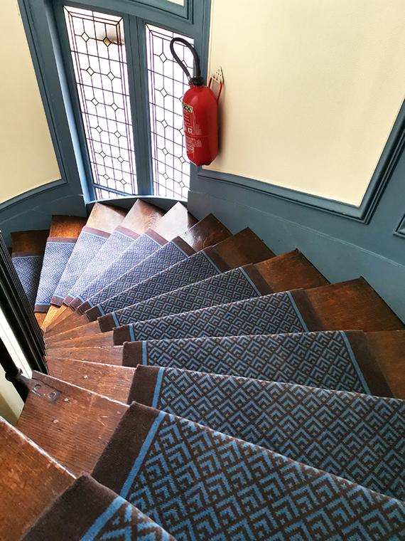 tapis bleu géométrique dans un escalier en bois