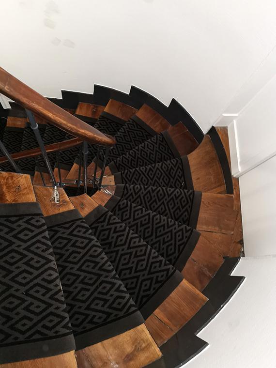 tapis d'escalier en bois tournant gris foncé aux motifs géométriques noirs