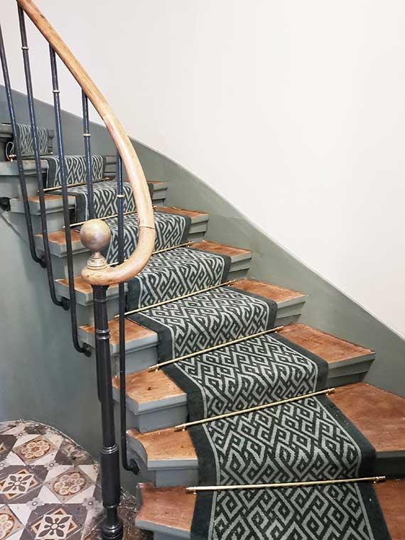 tapis vert géométrique dans un escalier en bois tournant