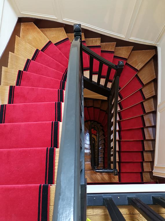 tapis d'escalier tournant rouge avec bordure noire