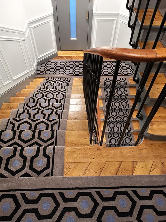 tapis au motifs nid d'abeille gris, bleu et noir dans un escalier droit en bois