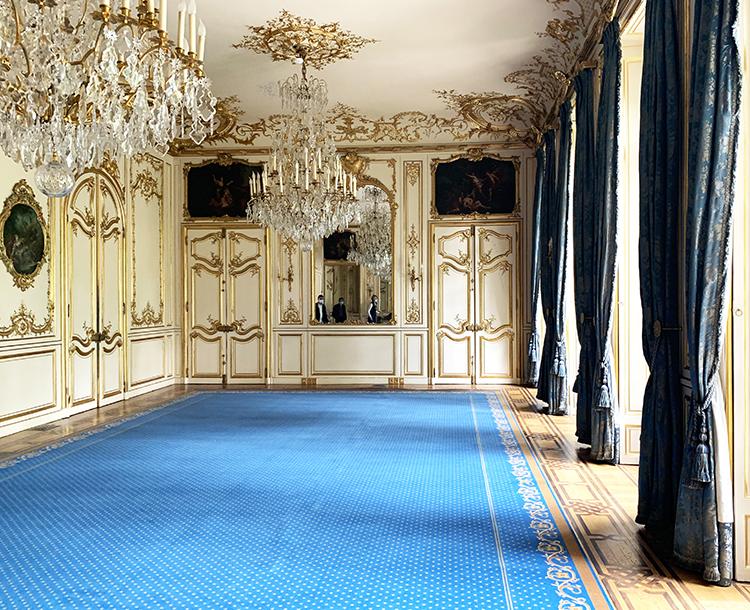 tapis bleu dans une pièce à moulures dorées