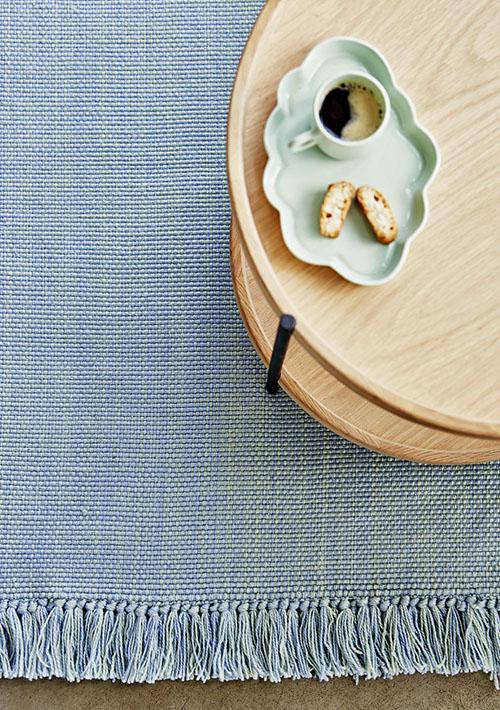 tapis bleu gris et table en bois
