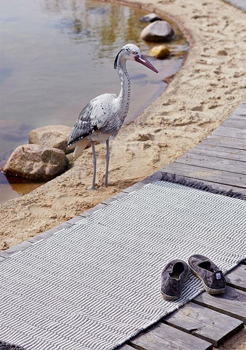tapis sur une plage avec un héron