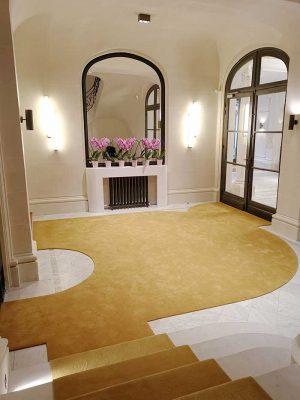 hall avec un tapis jaune et cheminée