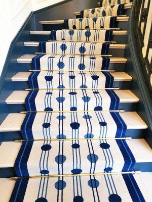 tapis à pois bleus et lignes noires posé dans un escalier en pierre
