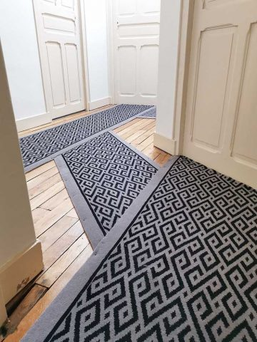 tapis noir et gris géométrique dans un couloir d'immeuble