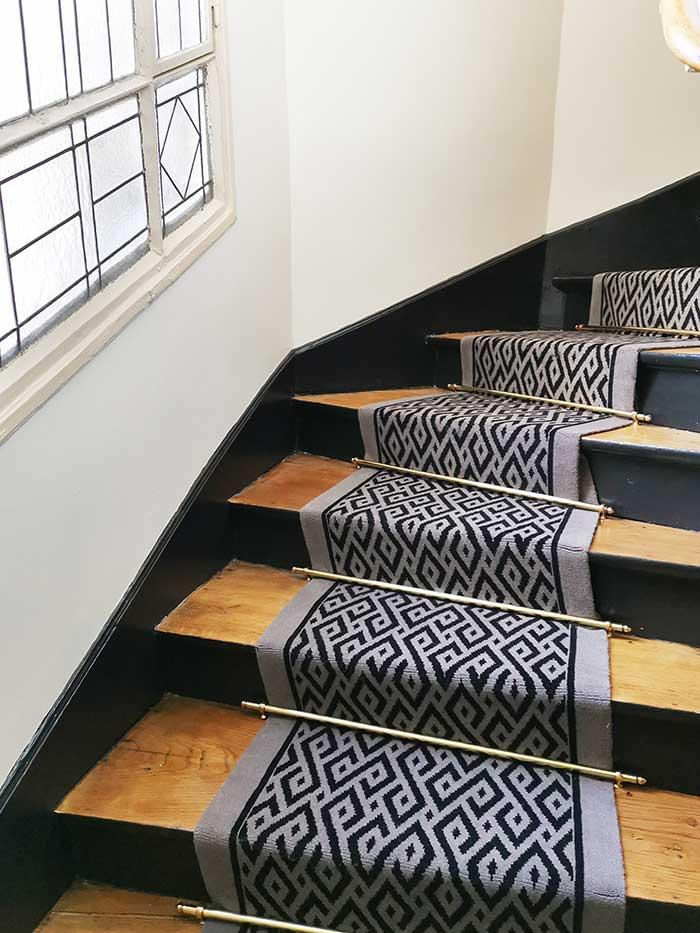 tapis graphique noir et gris dans un escalier en bois