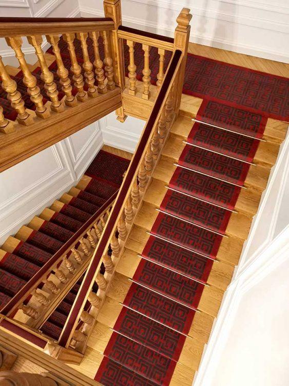 escalier en bois avec tapis rouge